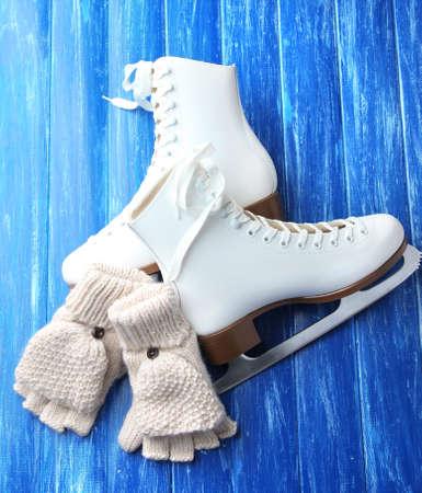 fingerless gloves: Wool fingerless gloves and skates for figure skating, on wooden