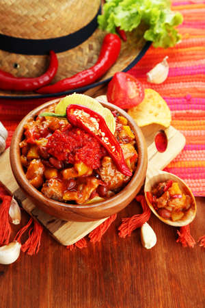 Chili Corn Carne - traditional mexican food, in wooden bowl, on napkin, on wooden  photo