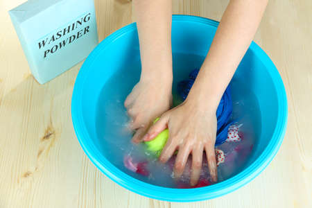 Hand washing in plastic bowl on wooden table close-up photo