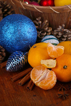 Christmas tangerines and Christmas toys on wooden table close-up photo
