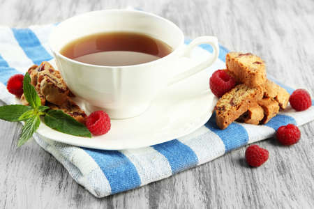 Cup of tea with cookies and raspberries on table close-up photo