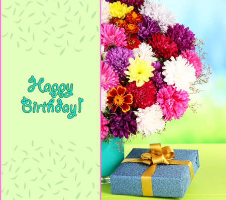 Beautiful bouquet of chrysanthemums on table on bright background photo