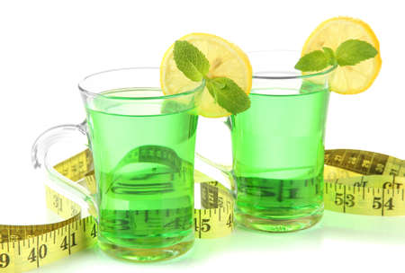 Two transparent cups of green tea and measuring tape close up photo