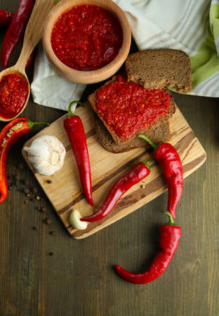 Composition with salsa sauce on bread,, red hot chili peppers  and garlic, on napkin,  on wooden background photo