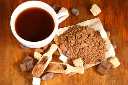 Cocoa in cup and coca powder on wooden table photo