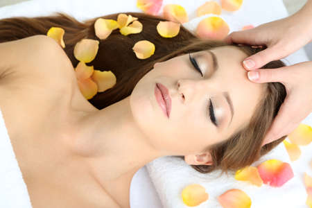 facial treatment: Beautiful young woman during facial massage in cosmetic salon close up Stock Photo