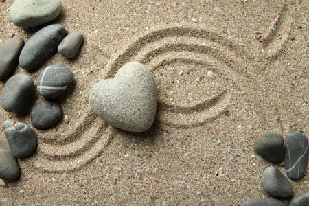 coldblooded: Grey zen stone in shape of heart, on sand background
