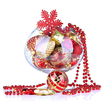 Glass bowl filled with Christmas decorations, isolated on white photo
