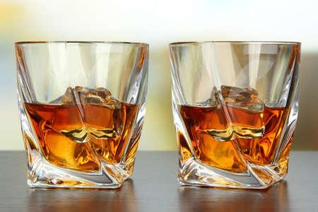 Glasses of whiskey, on bright background photo