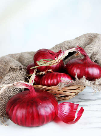 close up of onions in a basket: Fresh red onions in wicker basket on table close up Stock Photo