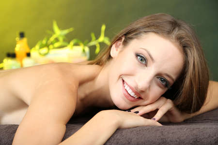 Beautiful young woman on massage table in cosmetic salon on color background Stock Photo - 23346457