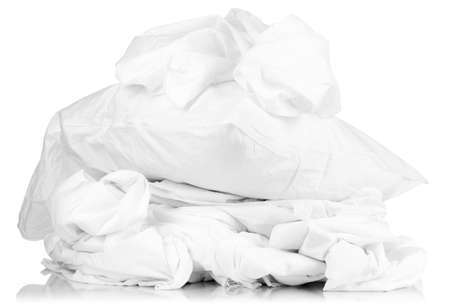 laundry concept: Rumpled bedding sheets and pillow isolated on white Stock Photo