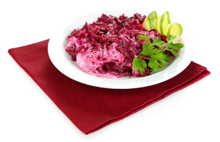 Beet salad on plate on napkin isolated on white photo