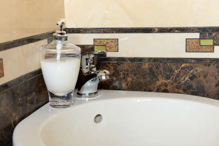 fixture: Ceramic sink with chrome fixture, close up Stock Photo