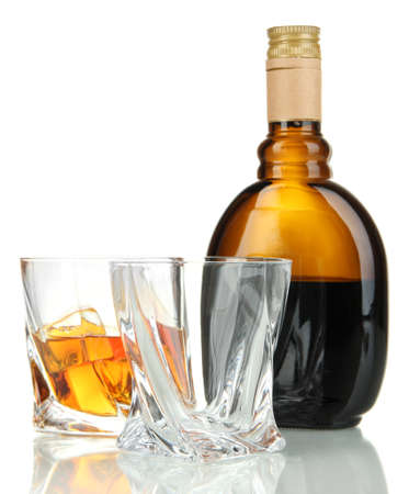 Glasses of whiskey with bottle, isolated on white   photo