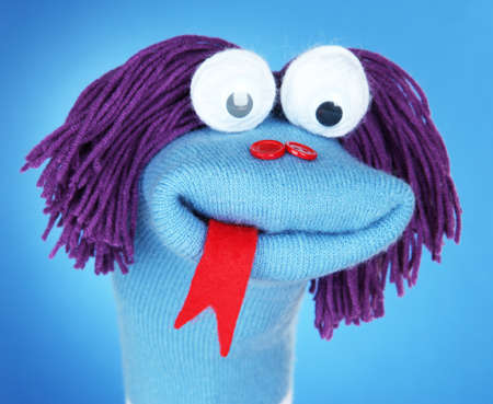 Cute sock puppet on blue background photo