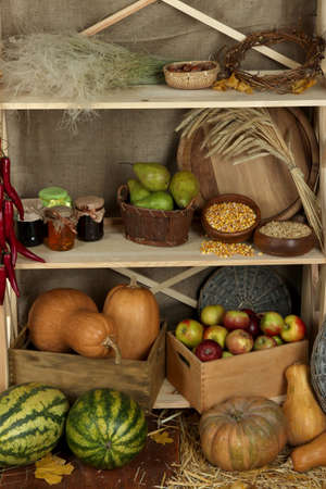 Fruits and vegetables with jars of jam and bowls of grains on shelves close up photo