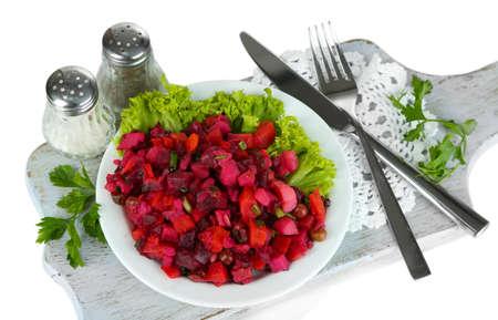 Beet salad on plate on napkin on wooden board isolated on white photo