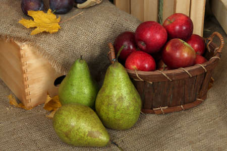Ripe fruits in basket on sackcloth background photo