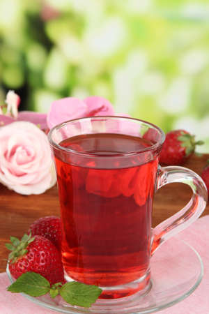 Delicious strawberry tea on table on bright background photo
