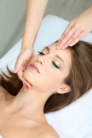 Beautiful young woman during facial massage in cosmetic salon close up Stock Photo - 24173818