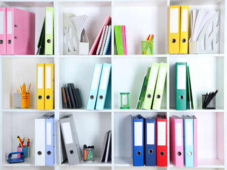White office shelves with folders and different stationery, close up photo