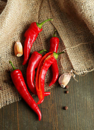 Red hot chili peppers  and garlic, on sackcloth,  on wooden background Stock Photo - 23536233