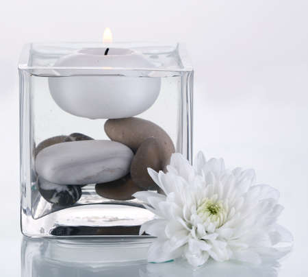 Decorative vase with candle, water and stones isolated on white photo