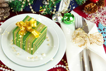 Small Christmas gift on plate on serving Christmas table background close-up photo