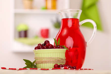 Pitcher and glass of cranberry juice with red cranberries on table  photo