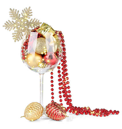 Wine glass filled with Christmas decorations, isolated on white photo