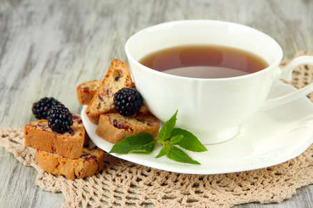 Cup of tea with cookies and blackberry on table close-up photo