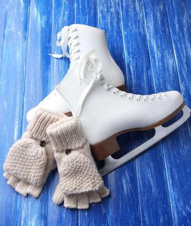 fingerless gloves: Wool fingerless gloves and skates for figure skating, on wooden background