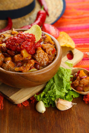 Chili Corn Carne - traditional mexican food, in wooden bowl, on napkin, on wooden background photo