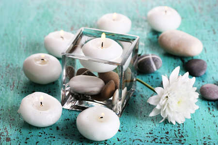 Decorative vase with candles, water and stones on wooden table close-up photo