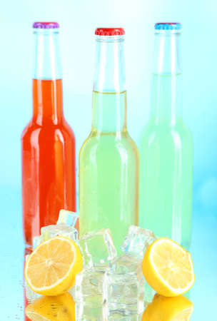 Drinks in glass bottles with ice cubes on blue background photo