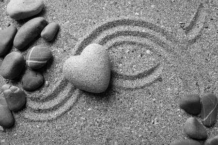 Grey zen stone in shape of heart, on sand background photo
