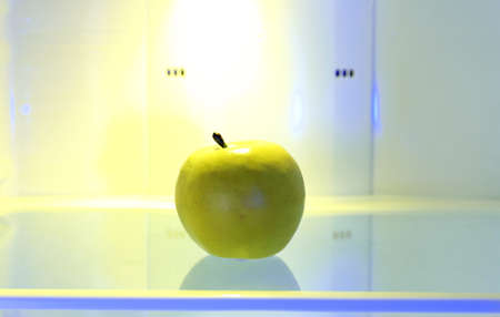 One apple in open empty refrigerator. Weight loss diet concept. photo