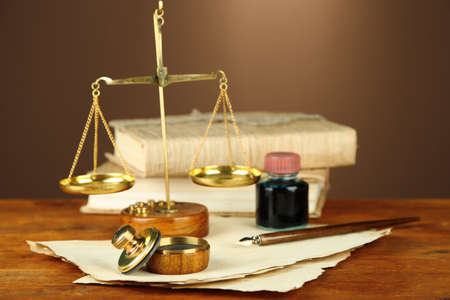 Wooden stamp, scales of justice and old papers on wooden table photo