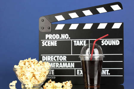 Movie clapperboard, cola and popcorn on blue background photo