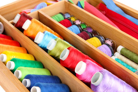 Colorful threads for needlework in wooden box close up photo