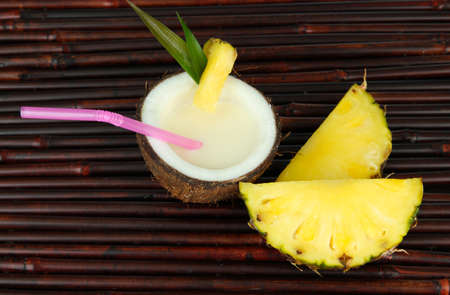 Pina colada drink in coconut, on bamboo mat background photo
