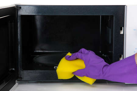 microwaves: Hand with sponge cleaning  microwave oven, isolated on white Stock Photo