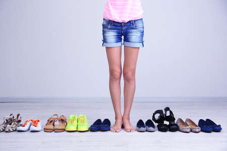 Girl chooses shoes in room on grey background photo