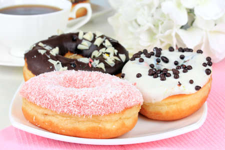sugared: Sweet donuts with cup of tea on table close-up Stock Photo