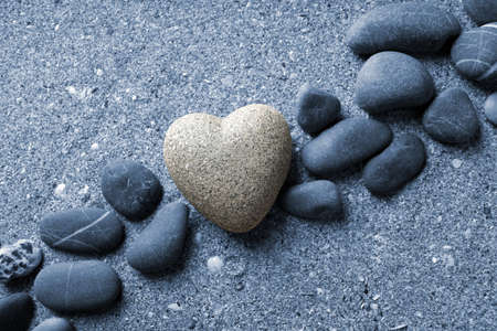 coldblooded: Grey stone in shape of heart, on sand background Stock Photo