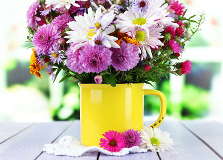 Wildflowers in mug on napkin on wooden table on window background photo