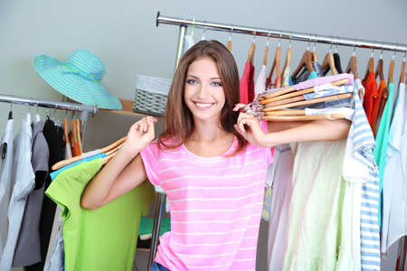 blouses: Beautiful girl with lots  clothes in room background Stock Photo
