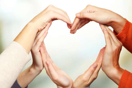sureness: Human hands in heart shape on bright background