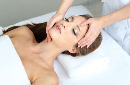 beautiful girl face: Beautiful young woman during facial massage in cosmetic salon close up Stock Photo